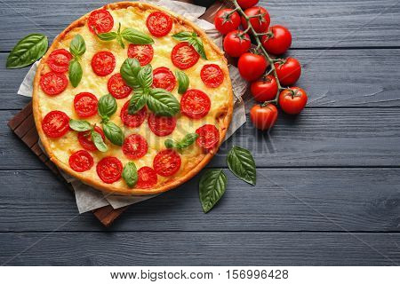 Fresh tasty pizza Margarita and tomatoes on wooden background, top view