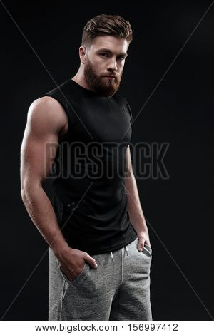 Side view of athletic man. he bury one's hands in one's pockets. isolated dark background