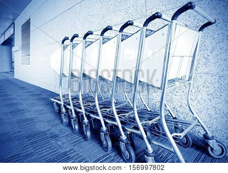 Luggage carts inside modern international airport, Blue tone chart.