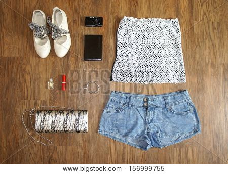 flat lay feminine clothes and accessories collage: lace top, denim shorts, clutch bag, shoes, camera, lipstick, lipstick, perfume and earrings poster