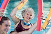 Smiling senior woman doing aqua fitness with swim noodles. Happy mature healthy woman taking fitness classes in aqua aerobics. Healthy old woman holding swim noodles doing aqua gym with young trainer. poster