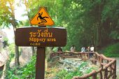 Sign showing a slippery area Thai and Chinese alphabet mean beware slippery. Obluang National Park Thailand. poster
