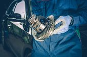 Broken Automotive Differential in a Hands of Car Mechanic. Replacement of Broken Car Elements. Car Maintenance. poster