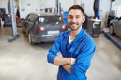 car service, repair, maintenance and people concept - happy smiling auto mechanic man or smith at workshop poster