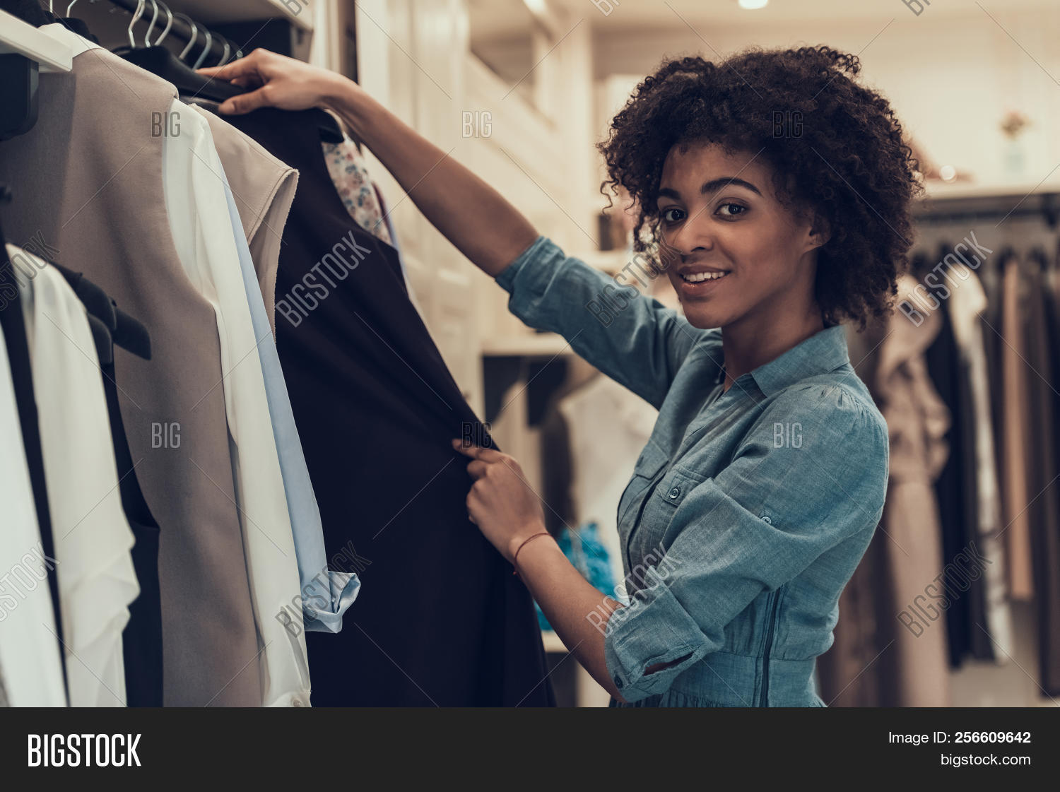 07fcff251e Smiling Young Woman Shopping in Clothing Store. Happy Beautiful Black Girl  choosing Clothes to Buy in Boutique inside Mall. Attractive african Woman  with ...