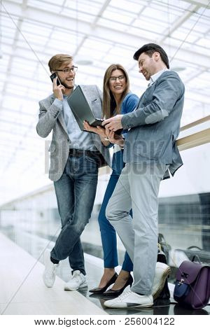 business colleagues using their gadgets standing in the office l