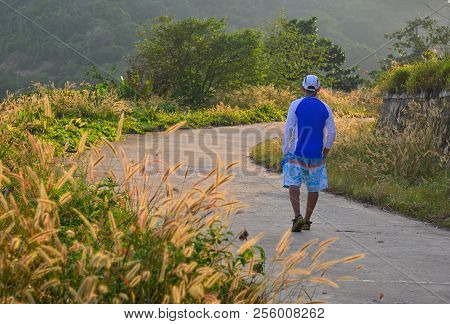A Man Walking On The Rural Road With Grass At Sunset In Summer Day.