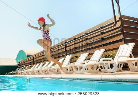 The Portrait Of Happy Smiling Beautiful Teen Girl Jumping At The Swimming Pool. Little Child At Blue