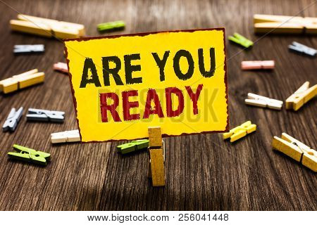 Handwriting text writing Are You Ready. Concept meaning Alertness Preparedness Urgency Game Start Hurry Wide awake Clothespin holding yellow paper note several clothespins wooden floor. poster