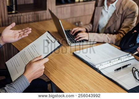 Business Man Holding His Resume And Explaining About His Profile To Two Senior Manager Sitting In Du
