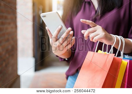 Consumerism, Shopping, Lifestyle Concept, Young Woman Holding Colorful Shopping Bags And Smartphone