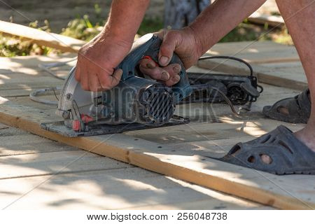 Carpenter Using A Circular Saw To Cut A Wood Board Formwork For The Fence.