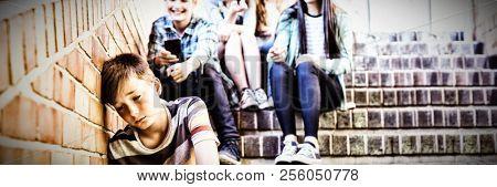 School friends bullying a sad boy in school corridor at school
