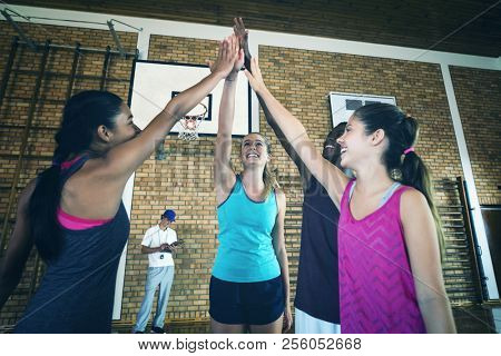Group of smiling high school kids giving high five in the basketball court