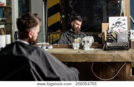 Man With Beard Covered With Black Cape Sits In Hairdressers Chair In Front Of Mirror. Hipster With B