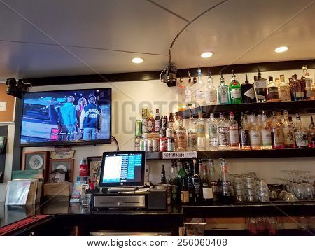 Honolulu - August 6, 2017: Movie Plays On Tv Inside Local Downbeat Diner Bar With Liquor On Display