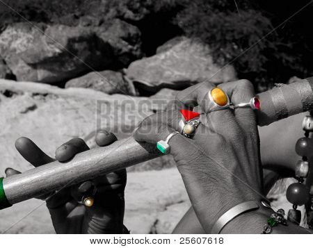 Man playing the flute in India on the side of the holy ganges