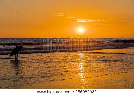 El Zonte, El Salvador. February 2018. A View Of A Surfer During A Colorful Sunset On The Beach In El