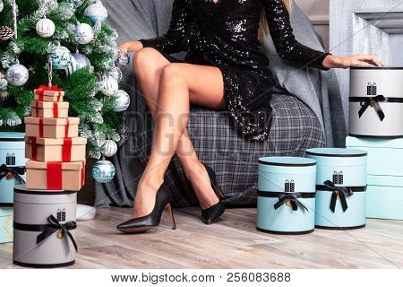 Beautiful woman with long slim legs in sexy black dress posing near the christmas tree