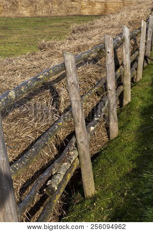 stacks of old last year straw fenced off by a primitive wooden fence poster