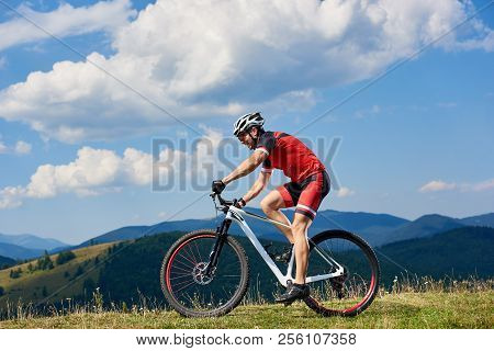 Athlete Sportsman Bicyclist In Professional Sportswear And Helmet Riding Cross Country Bicycle On Su