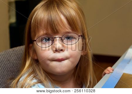 A Young Girl With Ocular Palsy Or Strabismus Tries On A Pair Of Metal Frame, New Glasses.  She Has H