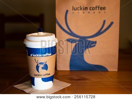 1 Septembre 2018, Wuhan China : A Coffee Cup With Sleeve Of Luckin Coffee On Wooden Table Background