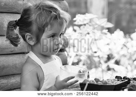 Cute Little Boy With Blond Hair Ponytail In White Pinafore Drinks Milk On Summer Day On Wooden Backg