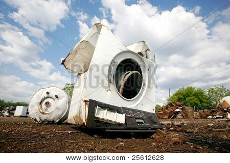 Old household appliances disposed of in metal scrapyard poster
