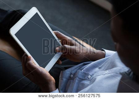 Male executive using digital tablet in futuristic office