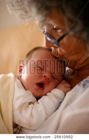 Grandma holding a baby and kissing it on it's head