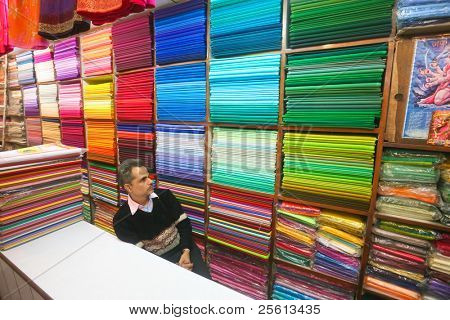 DELHI - JAN 15: Shopkeeper sitting in front of shelves of colourful fabric on January 15, 2008 in Delhi, India.  Textiles exports may touch $24 billion in 2010-11.
