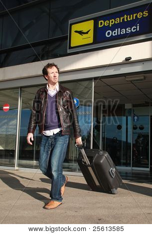 Young casual business business traveller exiting airport