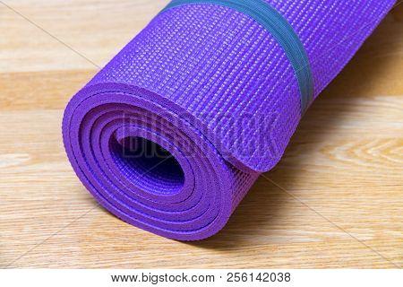 Yoga Mat On Wooden Floor. Selective Focus.