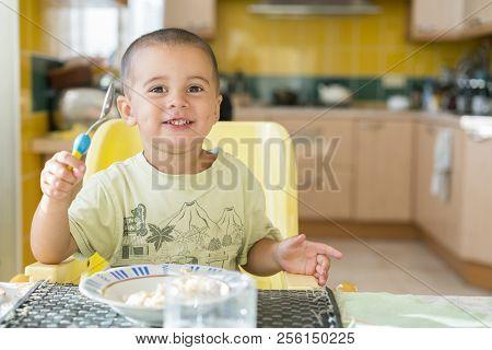 Happy Little Boy Eating Porridge. Little Boy Eating Breakfast At The Table. Happy Little Boy Is Havi