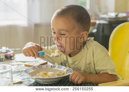 The Boy 2 Years Eats Porridge. Children's Table. The Concept Of The Child's Independence. Happy Litt