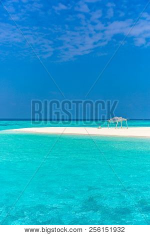 Amazing Blue Water In A Desert Island In A Blue Sky Day With A Small Wood Hut.