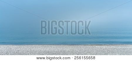 Black Sea Pebble Shore And Fog That Hides Horizon. Calm Morning On The Sea Shore. Tranquil Scenery.