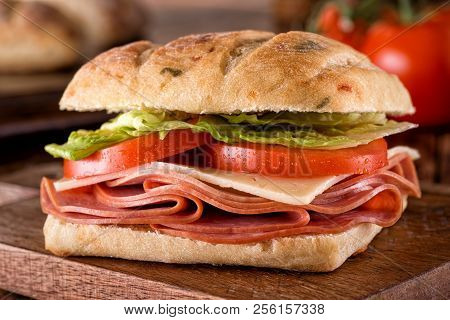 A Delicious Deli Sandwich On Cheddar Jalapeno Ciabatta Bread With Lettuce And Tomato.