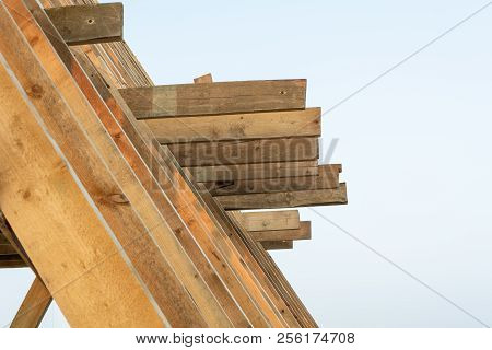 Single Family Home Construction. Building A New Wood Framed House. Wooden Rafters Against The Blue S