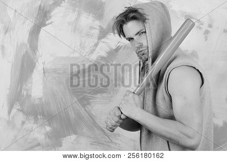 Guy In Grey Sleeveless Hoodie Holds Bright Green Bat. Man With Hood On Head On Colorful Background,