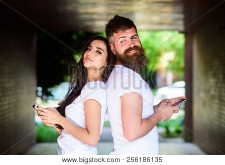 Send provocative message. Virtual cheating online. Couple ignore real communication. Couple chatting smartphones. Girl and bearded man stand back to back porch or underground. Suspect in cheating. poster