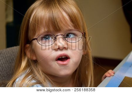 A Young, Blond Girl With Strabismus Or Ocular Palsy Tries On A Pair Of New Glasses.  Her Mouth Is Pa