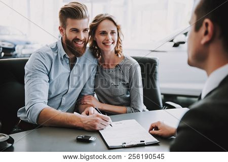 Portrait Of Successful Young Couple Buying New Car. Caucasian Man And Beautiful Smiling Woman Wearin