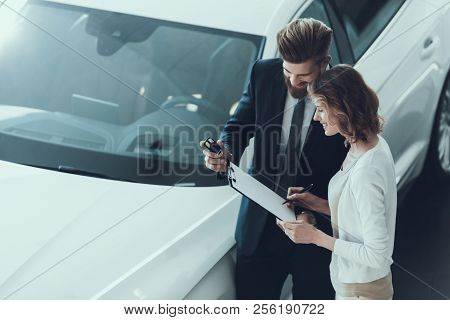 Car Salesman Consultant Showing Contract To Woman. Beautiful Young Woman Talking To Caucasian Handso