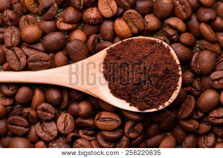 Ground Coffee In A Wooden Spoon. Ground Coffee In A Spoon On The Background Of Whole Coffee Beans.