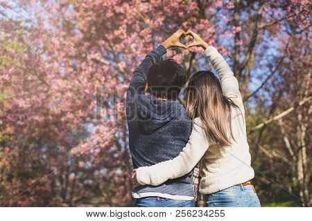 Young Couple Walking In The Park And Looking Cherry Blossoms Tree And Making Heart Shape With Hands