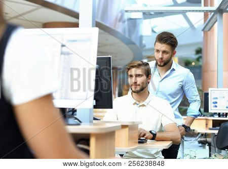 Group Of Young Confident Business People Analyzing Data Using Computer While Spending Time In The Of