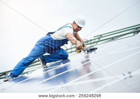 Construction Worker Connects Photo Voltaic Panel To Solar System Using Screwdriver. Professional Ins