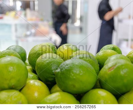 Closeup Of Fresh Limes With Blurred People In Kitchen